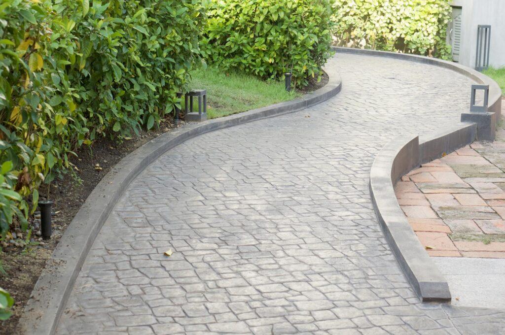a concrete walkway on the garden